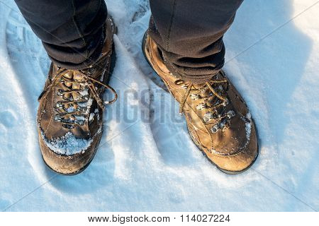 male hiker feet in old hiking boots on a snowy trail, top view