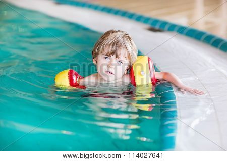 little kid boy with swimmies learning to swim in an indoor pool