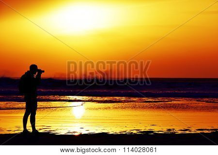 the silhouette of a young caucasian man taking a picture in front of the sea at dusk, against a colorful orange sky
