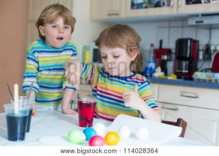 Two little blond kid boys coloring eggs for Easter holiday