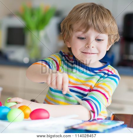 Little kid boy coloring eggs for Easter holiday