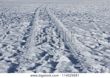 Wheel Track And Human Footprints On The Snow