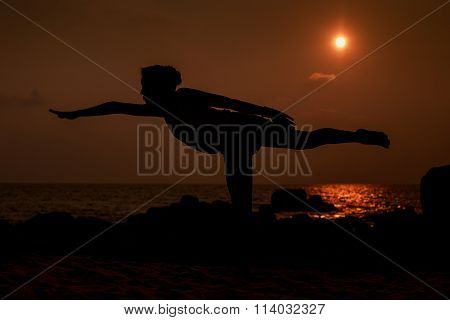 Gymnast Silhouette In Pose Leg Scale Against Sun Disk Over Sea