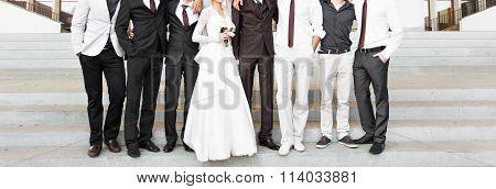 Handsome groom in suit hugging elegant bride and groomsmen
