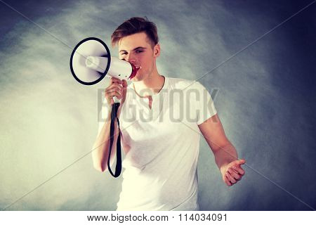 Young man shouting in megaphone.