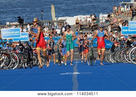 Triathletes Running With Bicycles In The Transition Zone