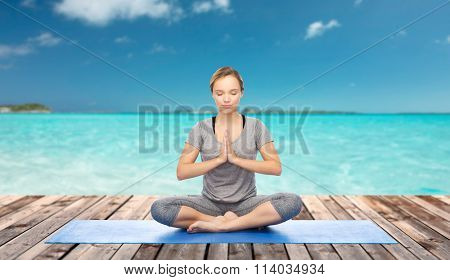 woman making yoga meditation in lotus pose on mat