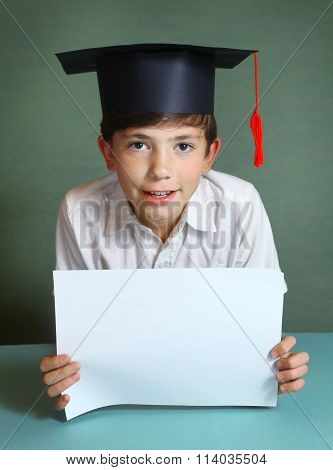 boy in graduation cap with white paper sheet in hands