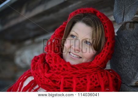 The Russian woman in a shawl warms hands near an izba