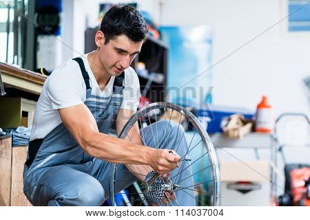 Man as bicycle mechanic working in workshop