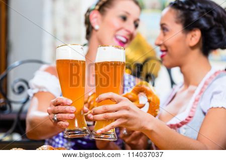 Girlfriends with Pretzel and Beer in Bavarian Inn eating and drinking