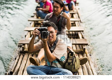 Taking Photo While Travel On Bamboo Raft