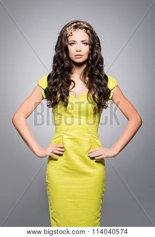 Beautiful, young brunette in bright dress wearing golden coronet over isolated background.