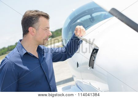 Man lifting flap on aircraft
