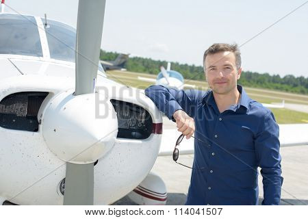 Portrait of man leaning on aircraft