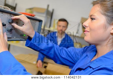 Worker adjusting dial on machine