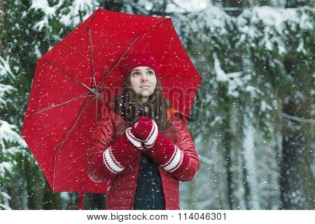 Winter outdoors portrait of smiling young woman holding fully collapsible umbrella in snowstorm