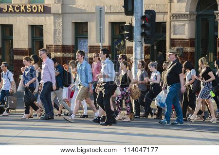 People walking across a busy crosswalk in Melbourne at sunset