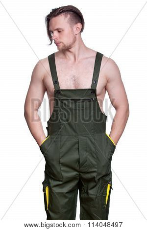 Young Strong Man With A Naked Torso In A Working Uniform Stuck His Hands In His Pockets