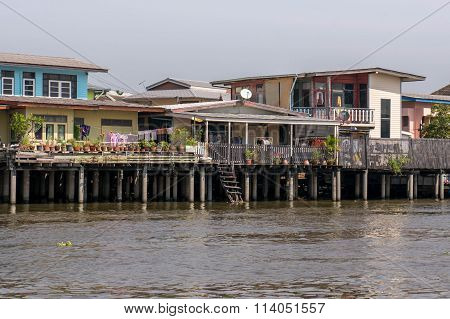 Traditional Stilt Houses On Chao Phraya's Riverbank