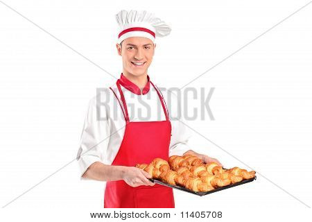 A Baker With Red Apron Holding Croissants