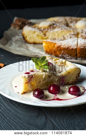 Piece of pineapple pie and cherries on white plate