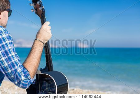 Man With Guitar Sitting On Coast And Looking Away