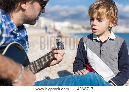 Son And Father Singing Song On Beach