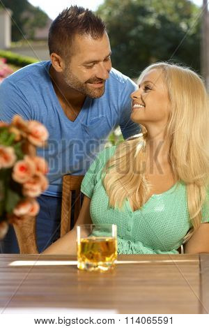 Portrait of romantic young married couple, summer, outdoors. Attractive, busty blonde woman with cleavage. Looking at each other.