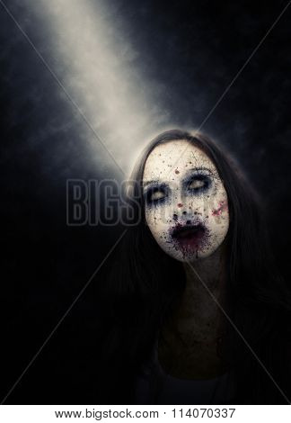 Portrait of Zombie Girl with Decayed Face and Blood Splattered Face Lit by Spotlight in Dark Studio with Copy Space