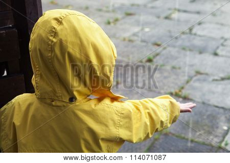 Little Child In Yellow Raincoat Playing With Water Drops