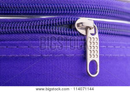 Pull Tab And Chain Of A Zipper On A Violet Suitcase
