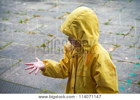 Little Child In Raincoat Playing With Raindrops