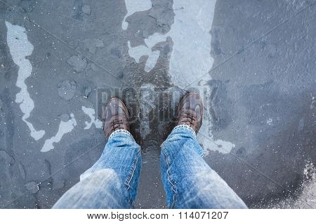 Male Feet Standing On Frozen Puddle With Thin Ice