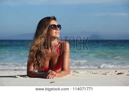 Woman in bikini and sunglasses laying at tropical beach