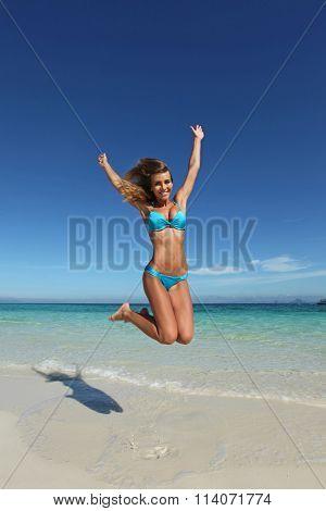 Beautiful woman in bikini jumping on tropical beach