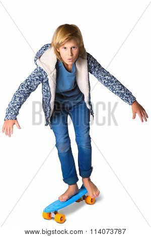 Cute blonde boy or teenager in full length casual style blue jeans posing with skateboard pennyboard