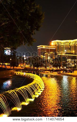 Fountains illuminated with lights at night time near Venetian Macao Resort Hotel