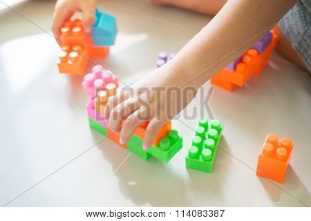 Boy Hands Playing With Colorful Plastic Blocks