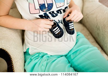 Pregnant woman holding small baby shoes