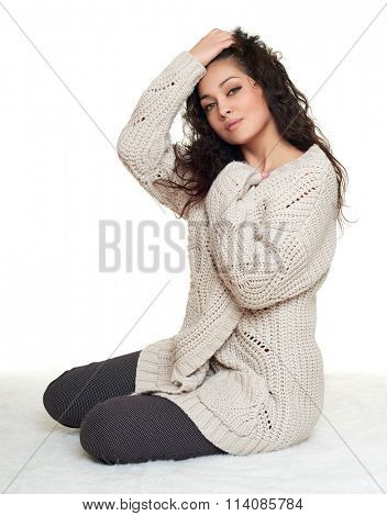 girl portrait in homelike dress sit on fur floor, white background