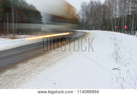 Motion blur of a speedy truck on a road turning