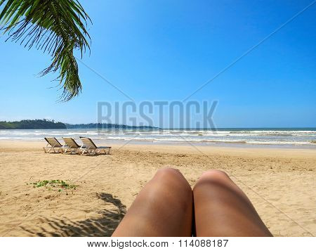 Beach view in selfie style with legs and palm leaf
