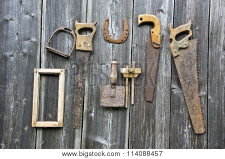 Rusty Vintage Carpenter Tools And Horseshoe Hanged On Wooden Wall