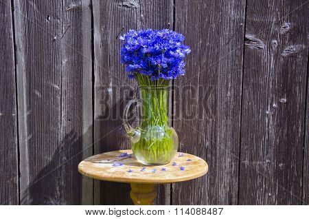 Cornflowers In A Jug Placed By The Wooden Wall Outdoors