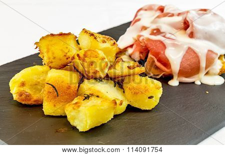 Roasted Potatoes With Ham And Cream Served  Black Slate Stone  Plate. Gourmet Food