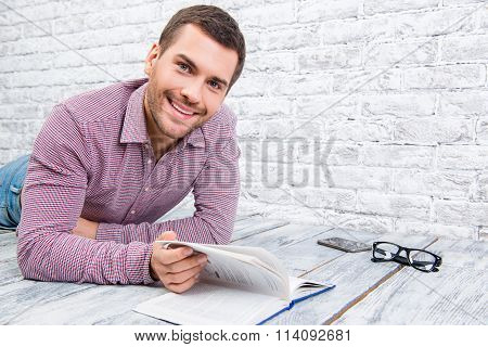 Cheerful Young Man Lying On The Floor And Reading Book