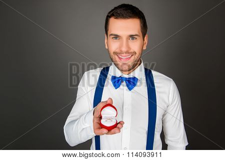 Smiling Man Holding A Bo With Wedding Ring