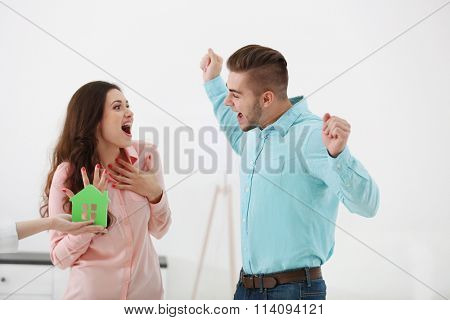 Hands of estate agent giving model of house to  couple, on light background