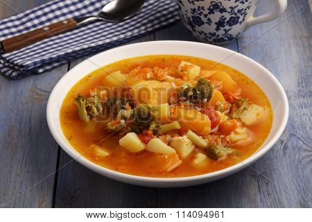 Italian vegetable soup minestrone on a rustic table
